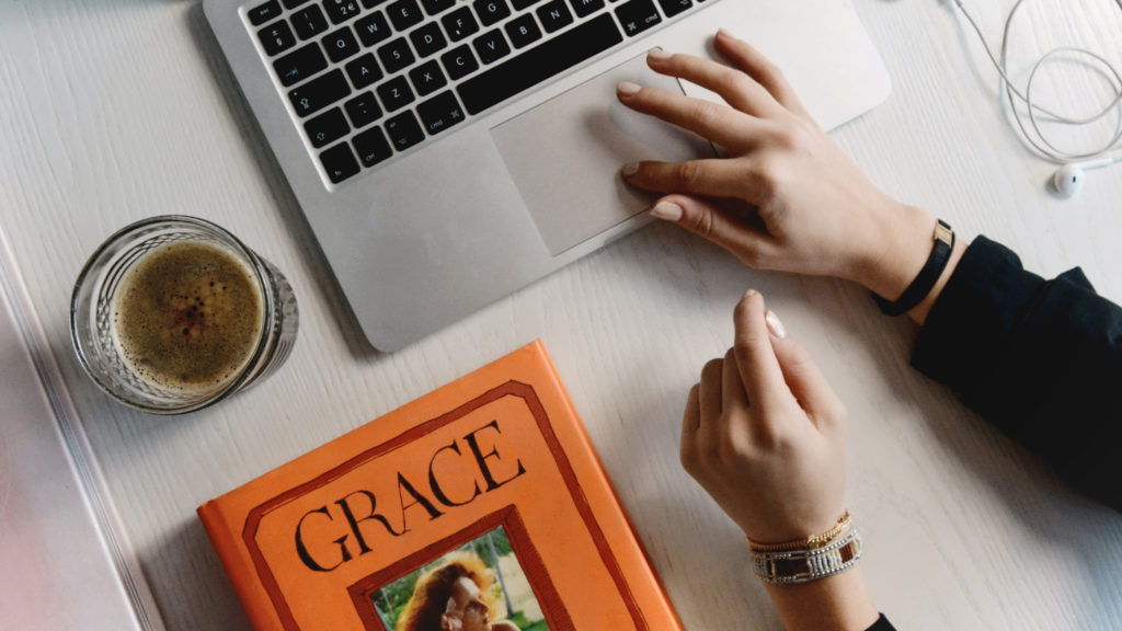 flat lay of girl clicking on a mac laptop. Grace book and ice coffee