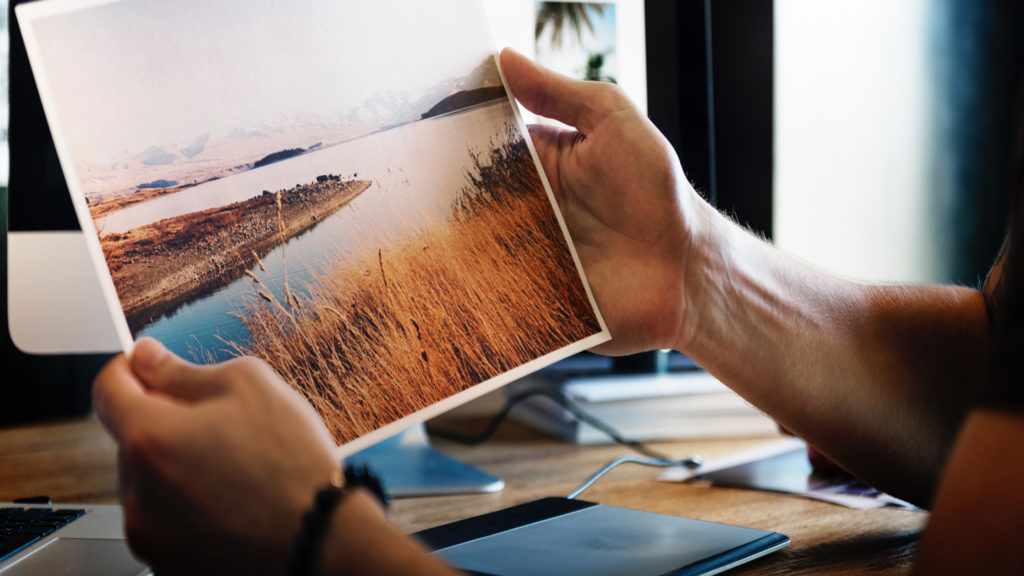 manly hands holding a picture of a lake