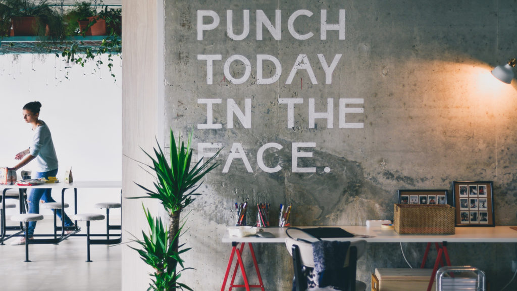 grey wall with white writing that says: Punch Today In The Face