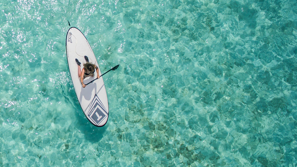 woman paddle boarding blue water