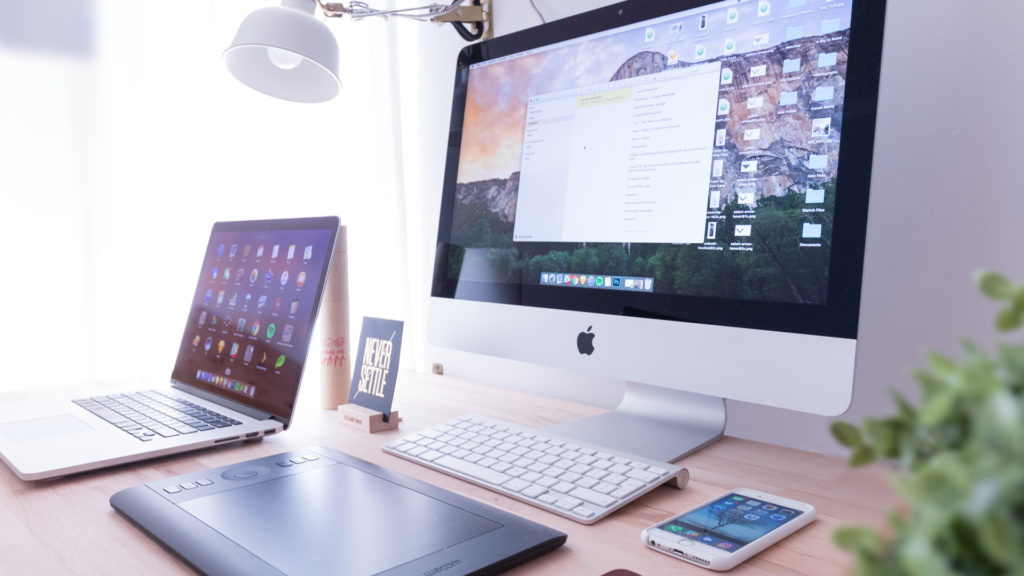 Image of desk with laptop desktop, iPhone and microsoft laptop.